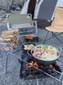 バーベキューでイスや薪の前にバーベキューコンロがあり鍋物や焼き物を火にかけている画像